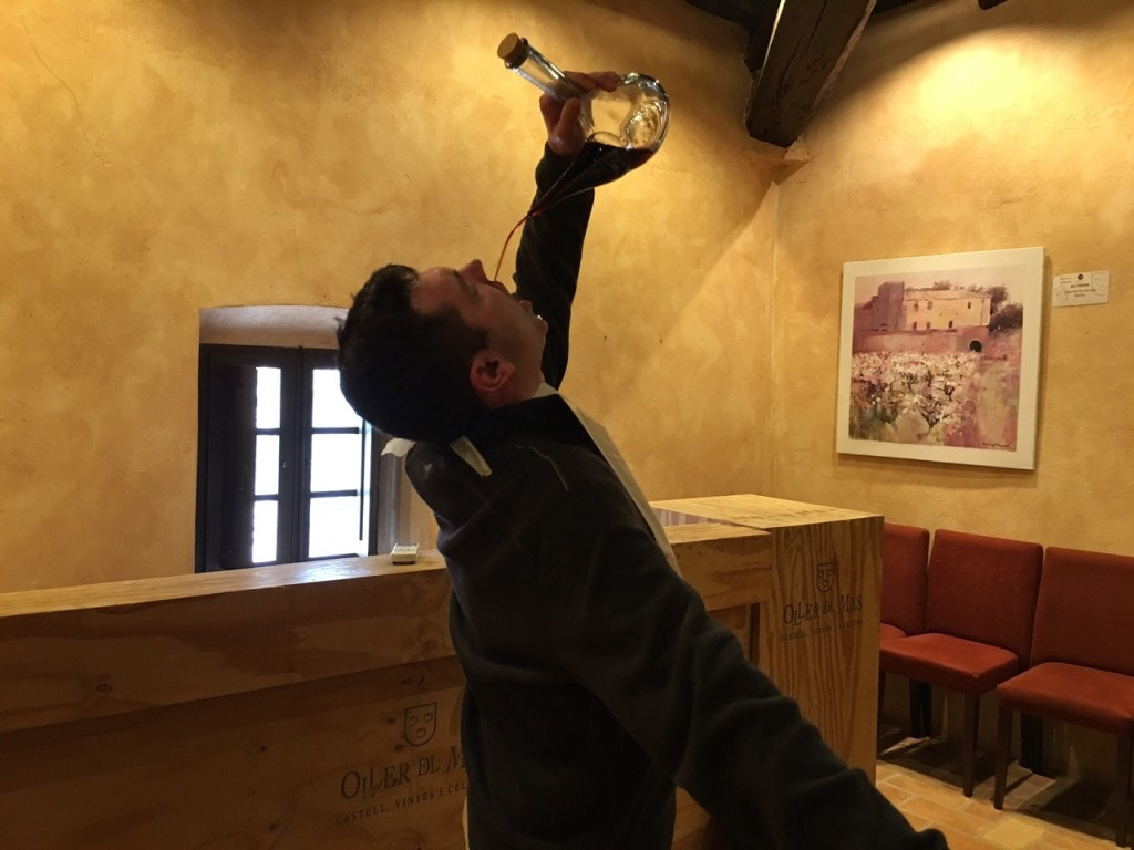 """Russell drinking wine from the porron. Luckily he wore a bib! - """"Montserrat: Mountain, Monastery, and Wine"""" - Two Traveling Texans"""