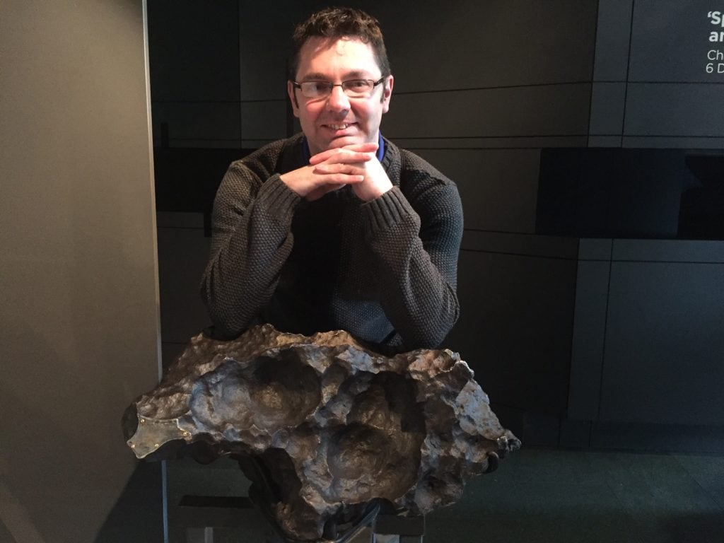 Russell with an asteroid on display at the Planetarium at the Greenwich Royal Observatory. It is about 4.5 billion years old.