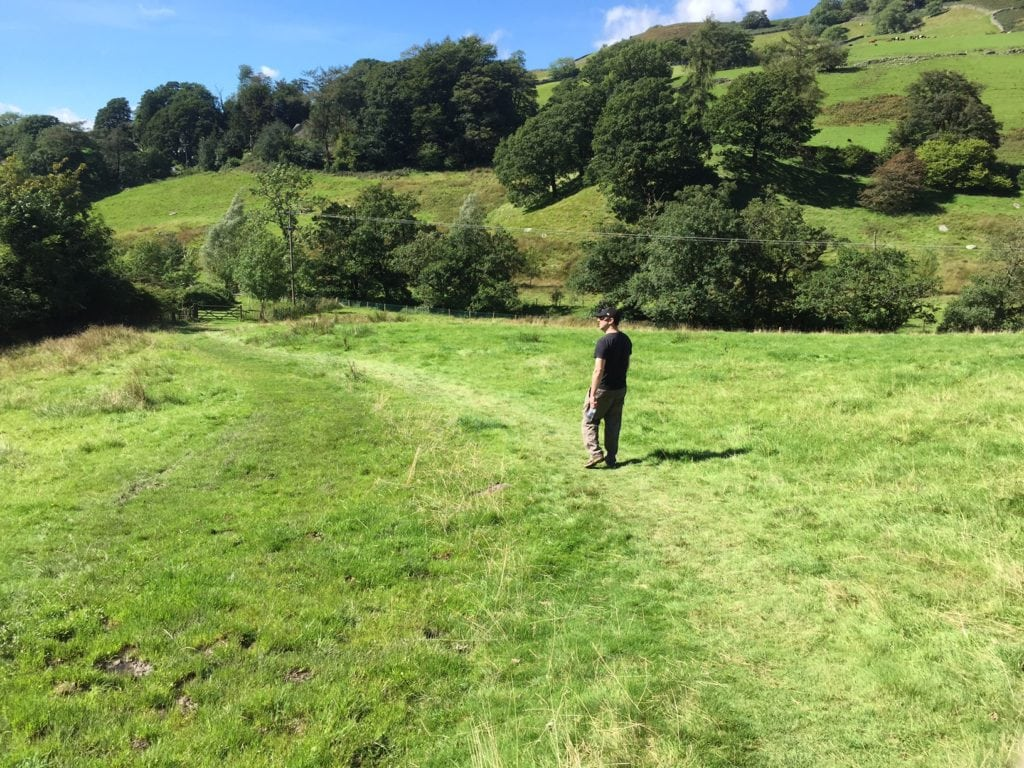 "Russell walking on the trail through a field. - ""An Introduction to England's Lake District"" - Two Traveling Texans"
