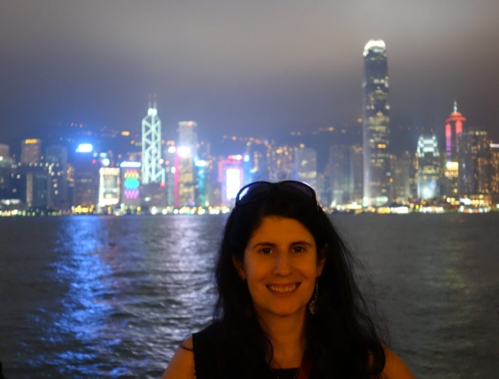 """Anisa with the Hong Kong skyline in the background. """"Random Acts of Kindness - Spark Hope Tag"""" - Two Traveling Texans"""