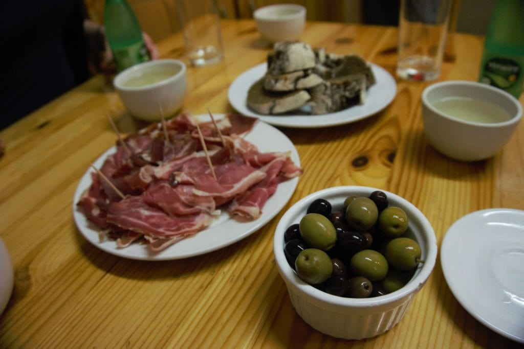 "Olives, ham, and the brown corn bread with more Vinho Verde served in ceramic cups. - ""Porto Food Tour: Taste the Local Specialties"" - Two Traveling Texans"