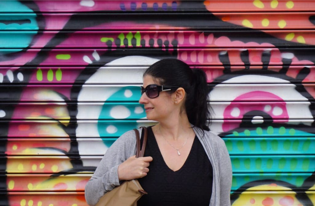 """Anisa posing by one of the colorful murals that is part of the Bushwick Collective. - """"Brooklyn Graffiti and Street Art Tour"""" - Two Traveling Texans"""