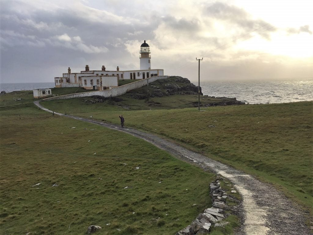 """The Neist Point Lighthouse with the sun trying to shine through the clouds. - """"Neist Point Lighthouse: Best Sunset Spot on Isle of Skye?"""" - Two Traveling Texans"""