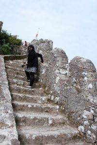 "Anisa climbing up the castle walls. You can see how windy it was, I couldn't keep the hair out of my face. - ""Why I Loved the Moorish Castle"" - Two Traveling Texans"