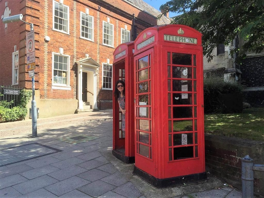 """Anisa in an iconic red phone booth in Norwich, England - """"Moving To England: How and Why I Did It!"""" - Two Traveling Texans"""
